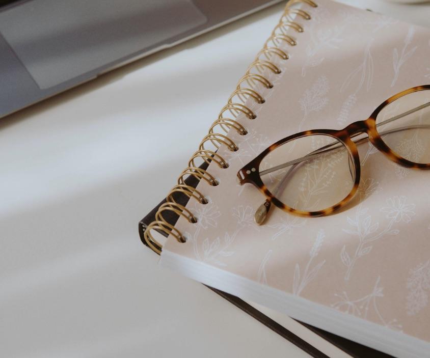 image d'un carnet avec une paire de lunette posée sur un bureau